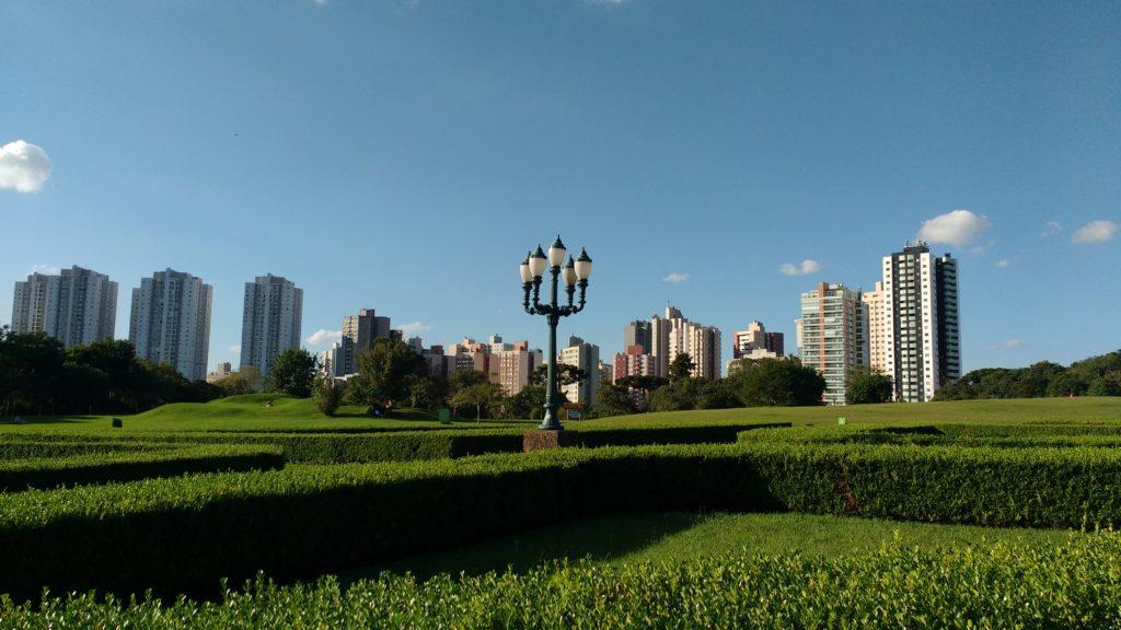 Os prédios de Curitiba se erguendo além do parque