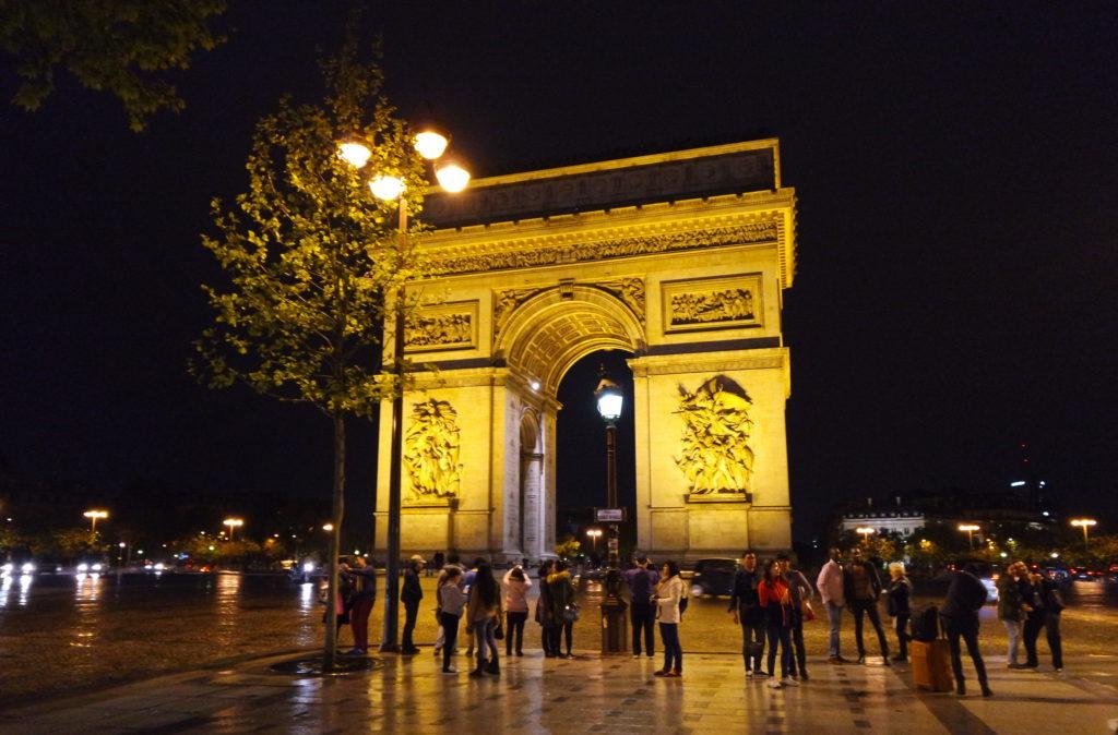 Arco do Triunfo iluminado, à noite, em Paris