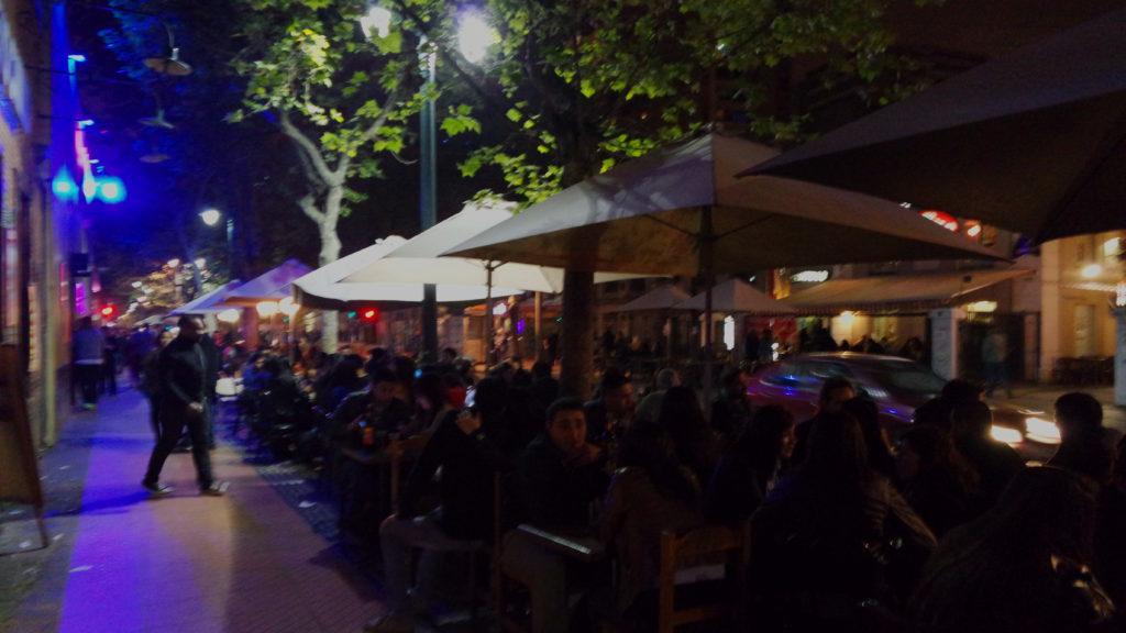 Cadeiras na calçada do bairro Bellavista de Santiago, à noite
