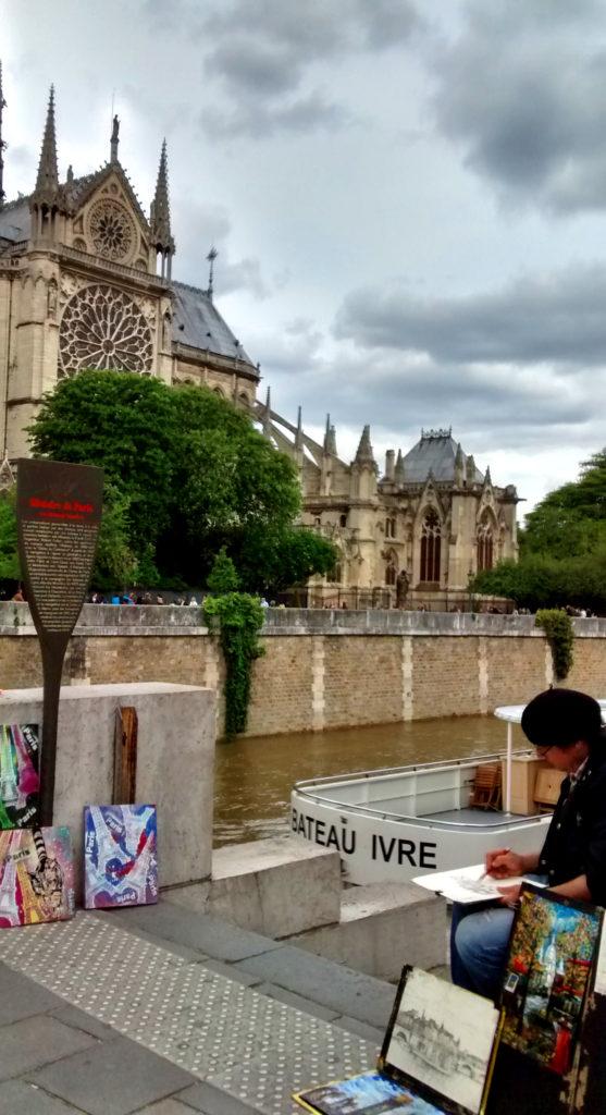 Artista desenhando à beira do Rio Sena, na margem oposta à Catedral de Notre Dame
