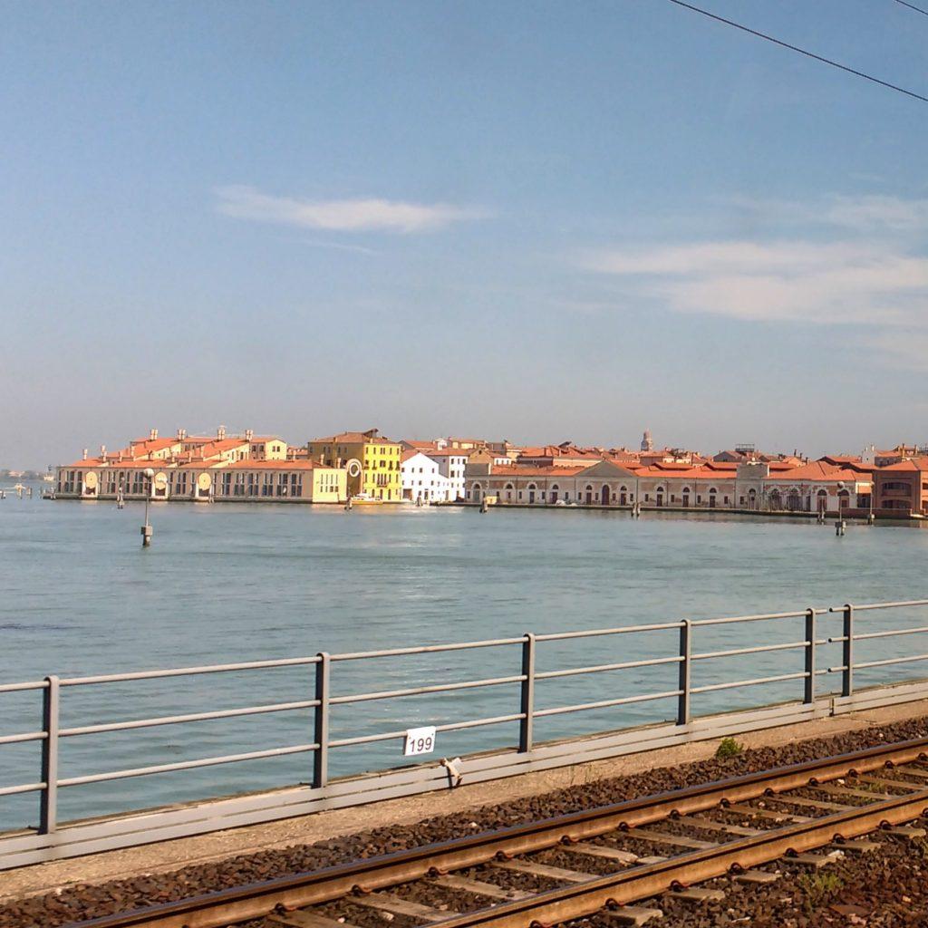 Chegando na estação de trem de Veneza, com os trilhos cortando as águas