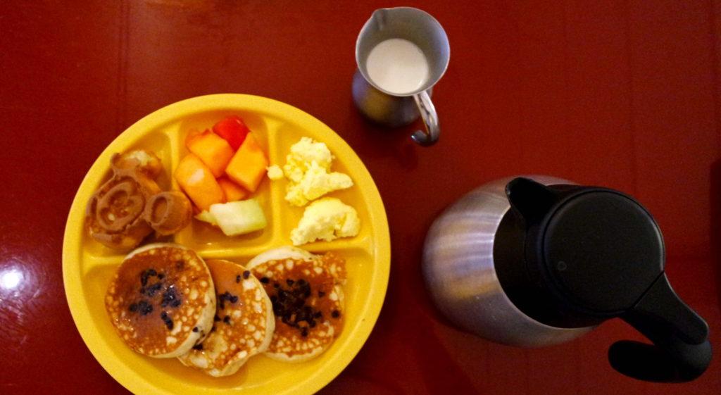 waffle, mais panquecas, ovos e frutas, acompanhados de leite