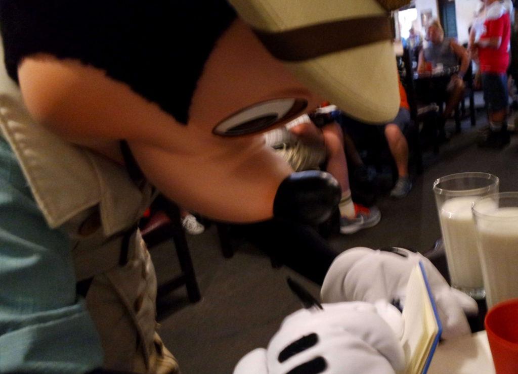 Mickey vestido em estilo safári assinando diário de viagem