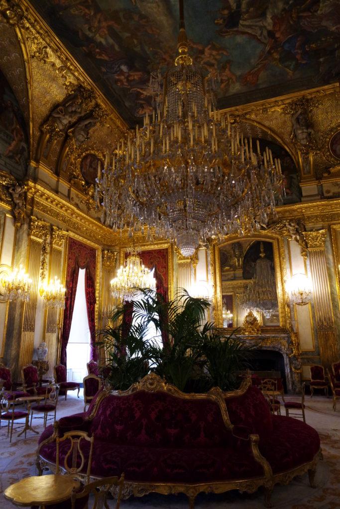 Ornamentação suntuosa com cristais e paredes em tom de outro, nos apartamentos de Napoleão, no Museu do Louvre