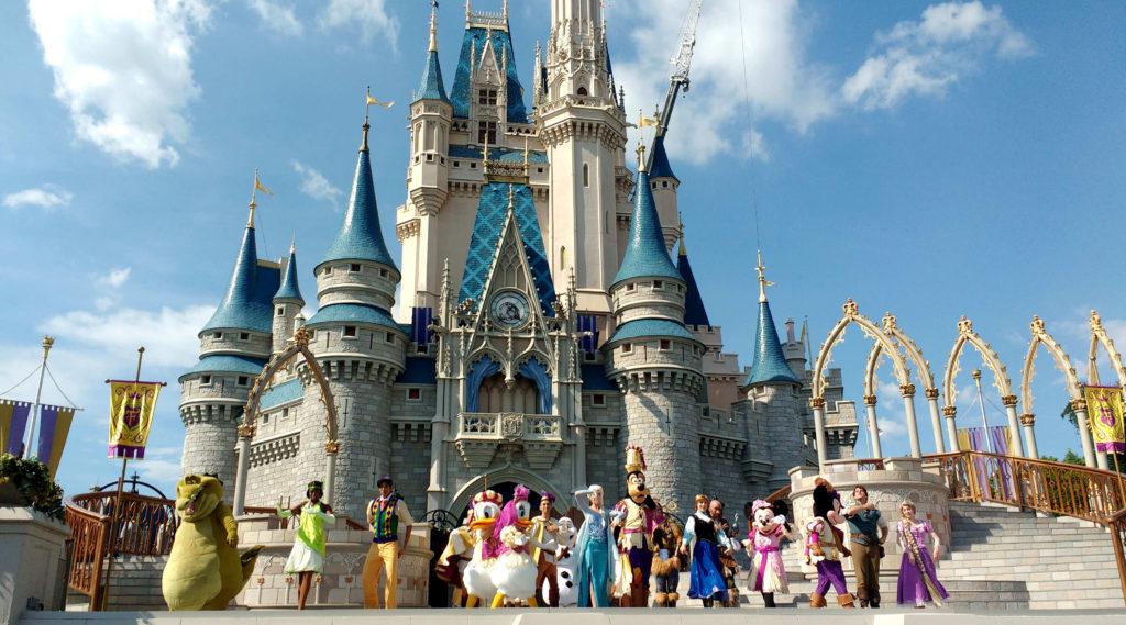 Magic Kingdom em um dia ensolarado, com os personagens Disney fazendo um show em frente a ele
