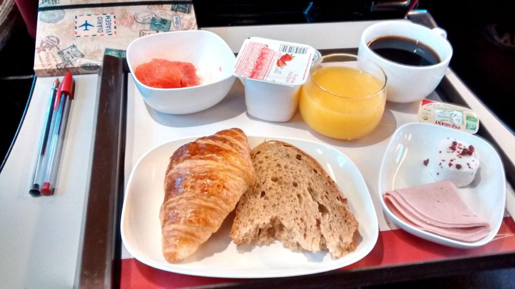 Café da manhã com croissant, pão, suco, iorgute