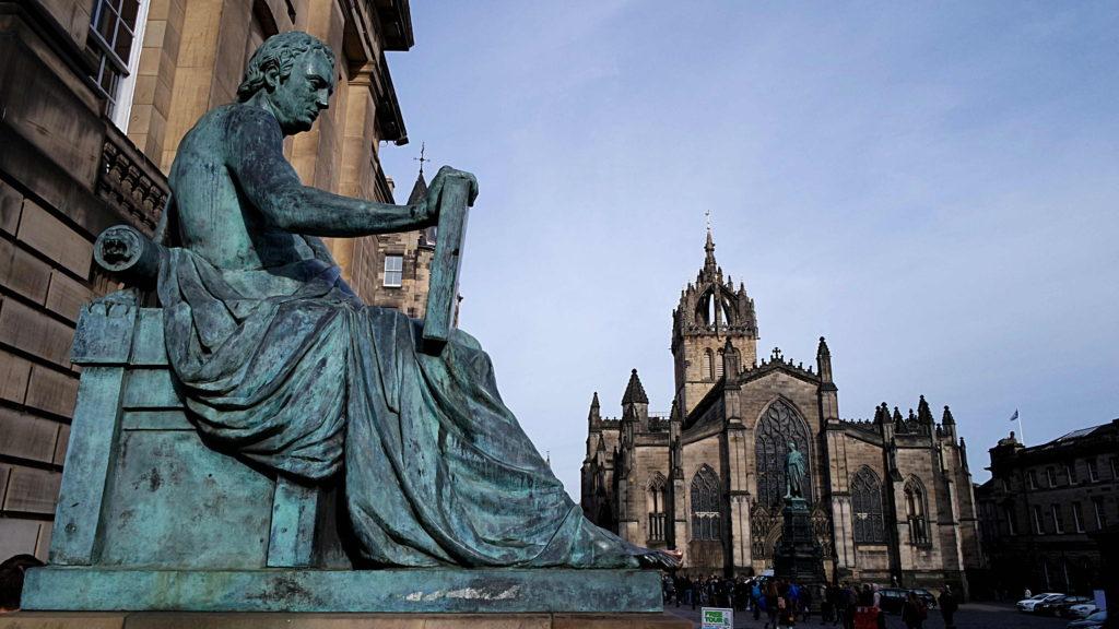 Estátua de David Hume e, ao fundo, a Igreja de St Giles