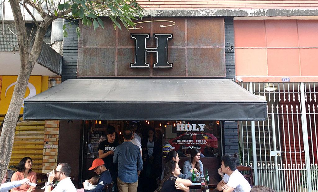 Holy Burger, com sua fachada discreta e as mesinhas na calçada