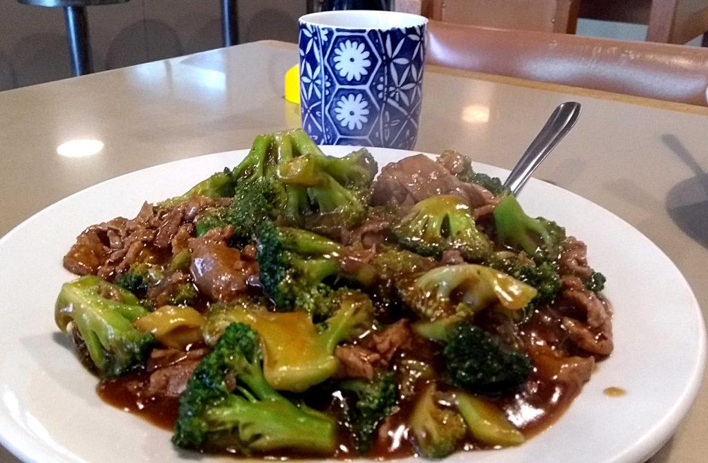 Carne com brócolis e o onipresente chá cortesia, ao fundo